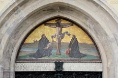 Tympanon der Eingangstür der Schlosskirche / Kirche der Reformation in Lutherstadt Wittenberg -  Jesus am Kreuz, Silhouette von Wittenberg - knieend Luther und Melanchthon.
