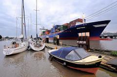 Sportboothafen / Yachthafen Brunsbütte - hinter der Schleuse im Nord-Ostsee-Kanal; Motorboot und Segelboote liegen am Steg, im Hintergrund fährt ein Containerfeeder in die Schleuse ein.