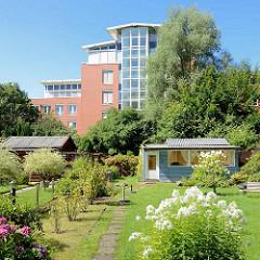 Kleingartengelände am Ufer der Kollau in Hamburg Niendorf - Schrebergartenlauben und moderne Verwaltungsgebäude.