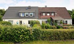 Doppelhaus mit unterschiedlich sanierter Fassade / Dach - Hecken; Architektur in der Stadt Norderstedt.
