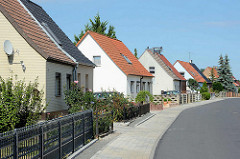 Doppelhäuser mit Satteldach und unterschiedlichen Zäunen am Vorgarten - Architektur in Wörlitz.
