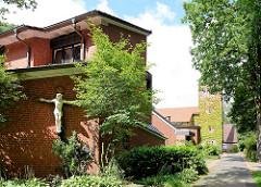 Gemeindehaus und St. Annenkirche in Hamburg Langenhorn / Ochsenzoll - Kruzifix an der Hauswand.