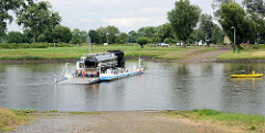Elbfähre über die Elbe in Coswig / Anhalt; die Gierseilfähre transportiert einen Tanklastzug über den Fluss. Im Vordergrund das Elbufer bei Wörlitz / Elbterrassen.