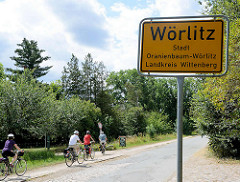 Ortsschild Wörlitz, Stadt Oranienbaum-Wörlitz - Landreis Wittenberg. FahrradfahrerInnen auf der Strasse nach Coswig / zur Fähre an den Elbterrassen.