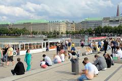 Anleger Jungfernstieg an der Binnenalster in der Hamburger Neustadt - Touristen sitzen auf den Bänken; Fahrgastschiffe der Alsterrundfahrt liegen am Anleger.