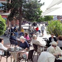Sommer in Hamburg Niendorf in der Fussgängerzone Tibarg - Menschen sitzen in der Sonne.