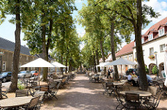 Baumallee - Aussengastronomie in der Sonne unter Bäumen, Tische mit Sonnenschirmen - Wörlitzer Markt.