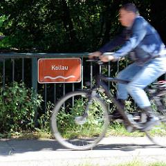 Brücke mit Schild Kollau in Hamburg Niendorf, schnell fahrender Fahrradfahrer.