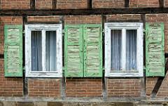 Alte Holzfensterluken / Fensterläden eines Fachwerkhauses in Lutherstadt Wittenberg - abblätternde Farbe.