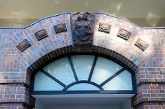 Terrakotta Dekor / nackte Frau eingelassen  über dem  Torbogen vom  Eingang der Neubauten auf dem Gelände des Eilbeker Krankenhauses in Hamburg.