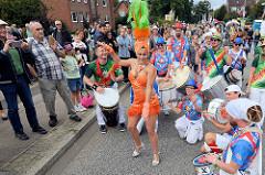 Karnevalsshow auf der Ulzburger Straße in Norderstedt - Musik im Brasil Rhythmus;  Trommler / Musiker spielen für eine Tänzerin.