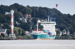 Das Feederschiff Ragna auf der Elbe vor Hamburg Blankenese - lks. der Leuchtturm Unterfeuer Blankenese, re. zwischen den Bäumen im Baurs Park das Oberfeuer - die beiden Leuchtfeuer bilden die Richtfeuerlinie Blankenese für elbaufwärts fahrende Schiff
