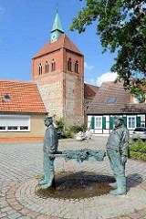 Fischerbrunnen von Arneburg - Kirchturm der romanischen Stadtkirche St. Georg.