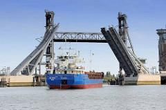 Ein Frachter fährt von der Rethe in den Reiherstieg in Hamburg Wilhelmsburg ein - die neue Brücke ist hochgeklappt, dahinter ist die alte Hubbrücke hochgefahren.