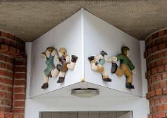 Umgesetzer alte Keramikdekoration - Symbole für Toilette, laufende Mutter mit Tochter - rennender Vater mit Jungen; Bedürfnisanstalt Lohbrügger Markt in Hamburg Lohbrügge.