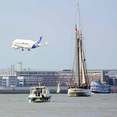Schiffe auf der Elbe vor Hamburg Finkenwerder - ein Airbus Beluga setzt zur Landung an.