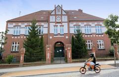Backsteinarchitektur mit Uhr im Giebel - Grundschule in Arneburg, Mofafahrer.