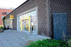 Eingang der ehem. Postbank an der Bergedorfer Straße in Hamburg Bergedorf. Kunst im Öffentlichen Raum - Steinrelief / Steinblock an der Hausfassade.