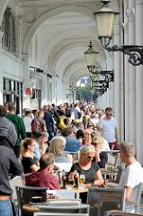 Aussengastronomie - Gäste an Tischen in der Sonne in den Hamburger Alsterarkaden - Touristen; im Hintergrund der Jungfernstieg.