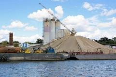 Industriebetrieb mit Silos und Schüttgut am Ufer vom Elbe-Havel-Kanal bei Genthin.