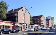 Ladenzeile im Flachbau-Stil der 1960er Jahremmit dahinterliegenden Wohnblocks  in der Weidestraße in Hamburg Barmbek Süd.