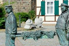 Fischerbrunnen von Arneburg - dahinter die Eichenholzbank Fischer un sin Fru, Künstler Horst Kahl.