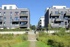 Blick vom Grünzug an der Wandse zu den Wohnhäusern im Parkquartier Friedrichsberg - eine Treppe führt in die Wohnanlage.
