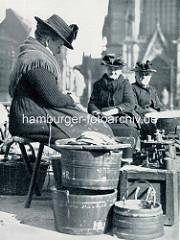 Marktfrauen / Fischverkäuferinnen auf dem Hopfenmarkt vor der Hamburger Nikolaikirche; Waage mit Gewichten.