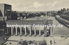 Alte Fotografie vom Bergedorfer Stadtbad ca. 1930; das Freibad liegt direkt an der Bille. Im Hintergrund sind die Schwimmbecken zu erkennen, dicht gedrängt liegen und sitzen die Badegäste bei sonnigem Wetter in der Badanstalt am Wasser.