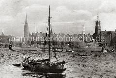 Ein Fischkutter fährt auf im Hamburger Hafen - der Steuermann des Schiffs steht im Heck; im Schlepp hat der Kutter ein Ruderboot,  Netze hängen über die Bordwand des Holzschiffs. Auf der Norderelbe fahren Barkassen und ein Schlepper.