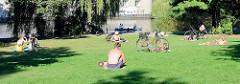 Grünzug am Ufer der Osterbek im Hamburger Stadtteil Barmbek-Süd; AnwohnerInnen ssitzen in der Sonne auf einer Wiese am Ufer vom  Osterbekkanal.