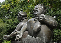 Bronzeskulptur Marktschreier am Lohbrügger Markt, Dr. János Enyedi 1989. Eine rundliche Marktfrau hält in der einen Hand das Wechselgeld und in der anderen eine Tüte mit Früchten. Dahinter steht der Marktschreier mit Mütze und preist seine Erzeug