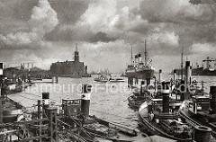 Hafenschlepper liegen an ihren Liegeplätzen bei den Vorsetzen; eine Hafenfähre hat die Elbe gekreuzt und fährt Richtung Sandtor-Anleger. An den Dalben auf Höhe des Kaisspeichers liegt ein Passagierschiff im Strom.
