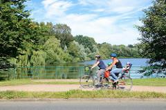 FahrradfahrerInnen auf dem Kupferdamm beim Kupferteich in Hamburg Farmsen; der Kupferteich wird von der Berner Au gespeist - früher wurde dort mit Hilfe eines wasserbetriebenen Kupferhammers z. B. Kupferdraht hergestellt.