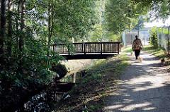 Holzbrücke über die Bille in Hamburg Bergedorf - Spaziergängerin mit Hunden.