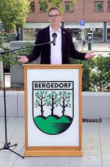 Bezirksamtsleiter Arne Dornquast am Rederpult mit Bergedorfwappen bei der Einweihung der Umgestaltung vom Lohbrügger Markt.