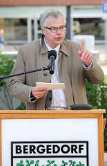 Staatsrat der Behörde für Stadtentwicklung und Wohnen Matthias Kock am Rederpult mit Bergedorfschriftzug bei der Einweihung der Umgestaltung vom Lohbrügger Markt.