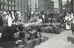 Marktgeschehen auf dem Hopfenmarkt an der Nikolaikirche; Körbe mit Gemüse / Zwiebeln - Marktfrauen, Kundin mit Korb.