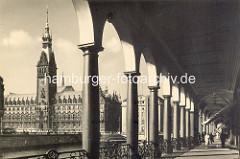 Säulengang der Alsterarkaden - Blick über die Kleine Alster zum Hamburger Rathaus.