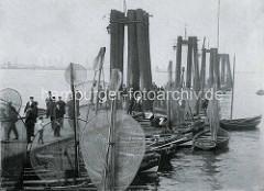 Anleger an der Fischauktionshalle in Hamburg Altona - Ruderboote mit Wurfnetzen und langen Keschern liegen am Ponton.