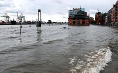 Das Hochwasser der Elbe hat die Kaimauer überspült und das Gelände des Hamburger Fischmarkts unter Wasser gesetzt. Auf der linken Bildmitte sind die Geländer der Kaianlage zu erkennen, dahinter die Wassertreppe zum Anleger, die teilweise unter Wa