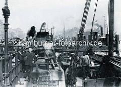 Dachziegel werden von Hand am Hamburger Binnenhafen / Vorsetzen verladen.