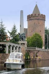 Ein Motorboot liegt vor der Stadtschleuse von Brandenburg an der Havel - im Hintergrund das Sowjetische Ehrenmal und der Steintorturm als Teil der ehem. Stadtmauer.