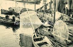 Hafenfischer bei ihren Booten im Hafen von Hamburg Altona - ein Fischer sitzt auf dem Bug eines Segelboots und repariert sein Wurfnetz.