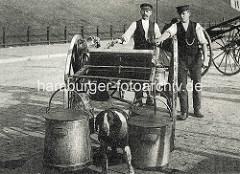 Zwei Milchhändler führen ihren Milchkarren an denen Milchkannen hängen - ein Arbeitshund ist als Zugtier angekettet.