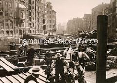 Altes Bild vom Anleger an der Holzbrücke beim Hamburger Nikolaifleet - Gemüsebauer laden ihr Gemüse aus einem Ewer aus und bringen es auf den naheliegenden Hopfenmarkt. Re. die Rückseite der Häuser an der Deichstraße, lks. die vom Cremon - im