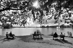 Sonnentag an der Hamburger Aussenalster - einige Segelboote sind auf dem Wasser; HamburgerInnen sitzen auf Holzbänken und blicken auf die Alster.