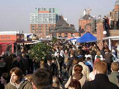 Jeden Sonntag findet der Hamburger Fischmarkt von 05:00 - 09:30 Uhr (im Winter 01.10. - 31.03.: 07:00 - 9:30 Uhr) statt. Besucher tragen gegen Ende der Marktzeit grosse Grünpflanzen nach Hause - Holländische Pflanzenhändler verkaufen die Palmen d