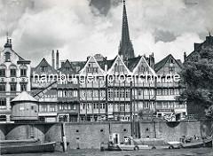 Kaimauer und Kran am Neuen Kran in der Hamburger Altstadt - Motorboot und Schute im Zollkanal; auf der Straße Fuhrwerk und Handkarren - hinter den Hausgiebeln der Kirchturm der St. Nikolaikirche.