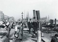 Alte Hafenszene an den Hamburger Vorsetzen am Binnenhafen - ein Milchhändler spült seine Milchkannen aus - im Hintergrund Wohngebäude an den Vorsetzen und Speichergebäude der Speicherstadt.